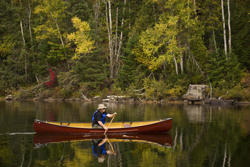 Elderly man canoeing  on Oxtongue Lake in autumn, Mukoka, Ontario, Canada.