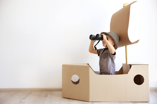 Little boy playing with cardboard ship on white wall background