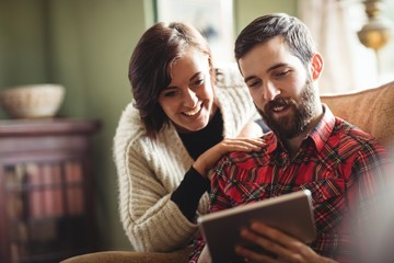 Couple using digital tablet in living room