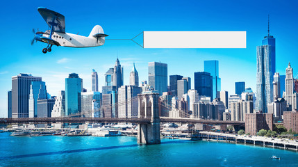 Wall Mural - airplane with a banner over manhattan