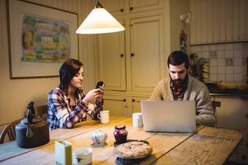 Couple using laptop and mobile phone