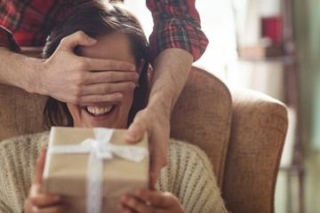 Man surprising woman with a gift in living room