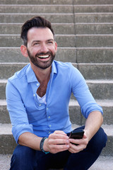 Smiling mature guy sitting outdoors with mobile phone
