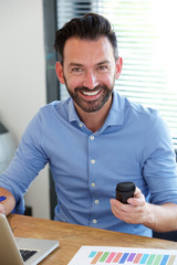 Cheerful middle aged guy sitting at his desk with mobile phone