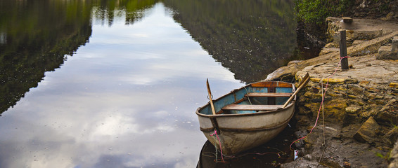 Old row boat, docked at the pier on a river reflecting it's surroundings.