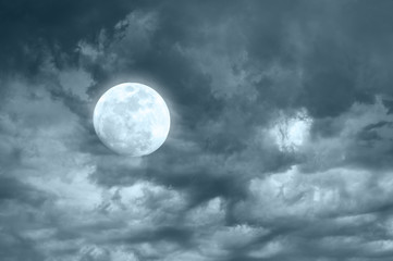 Amazing night sky with shining full moon and dramatic clouds