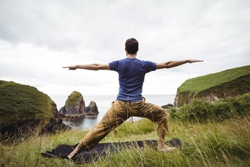 Rear view of man practicing yoga outdoors