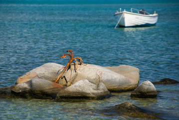 Wooden fishing boat floating on the colourful water. Cyclades, Greece. Beautiful seascape, large old anchor on a stone in the sea, boat in the background.