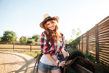 Happy redhead woman cowgirl preparing saddle for riding horse