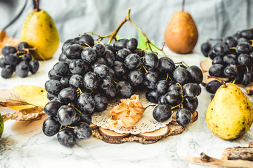 Fresh blue grapes and pears on a bright background