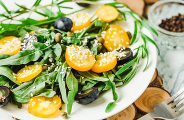 fresh green salad with arugula, yellow tomatoes, olives, grapes