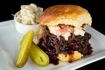 Smoked meat beef sandwich, with barbecue sauce, coleslaw served with potato mash and a pickle