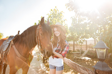 Smiling pretty young woman cowgirl in hat with her horse