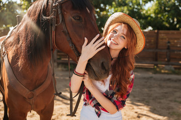 Happy woman cowgirl in hat standing and hugging her horse
