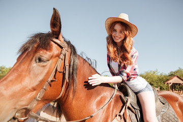 Happy pretty young woman cowgirl riding horse