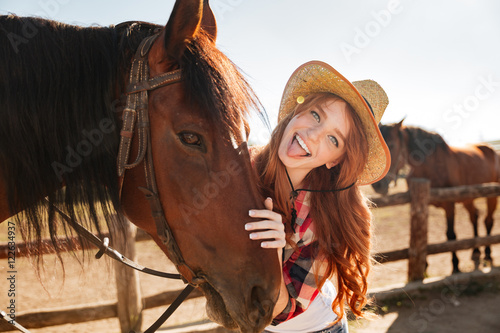 quotcheerful woman cowgirl standing with horse and showing