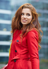 Beautiful stylish woman in a red coat. The city in the backgroun