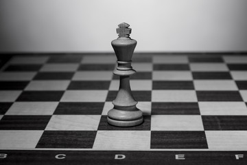 White chess king standing on chessboard alone