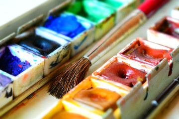 Box of watercolors with a brush. Tilt-shift effect applied.