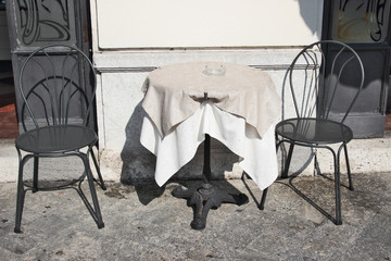 Restaurant table and metal chairs on the street, Bellagio, Italy.