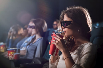 Attractive young woman watching a movie at the cinema
