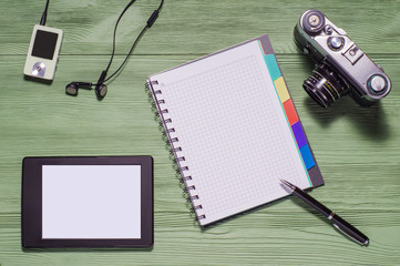 Top view of desktop.  Flat lay of personal stuff tablet pc, camera, notebook and other. Home office, work at home.  Mock up consisting of tablet pc in landscape orientation and blank notebook.