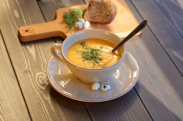 Pumpkin and lentil soup on dark wooden background. Halloween treat.