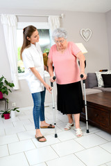 young physiotherapist nurse helping an elderly women physical rehabilitation at home