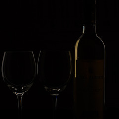 bottle of wine and two glasses on black back
