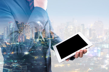 double exposure of businessman using tablet with blur city night