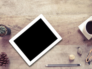 Tablet with cup of coffee , glasses and pencil on wooden table background.business concept.