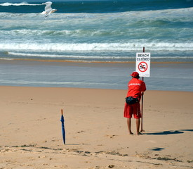 A sign reads beach closed. No swimming flag on the beach before/after storm.
