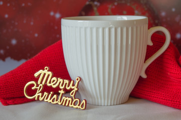 White Cup of coffee and a knitted red scarf, the words Merry Christmas