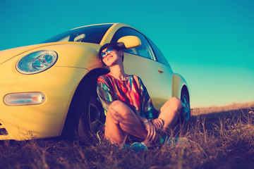 beautiful girl sitting near the car at sunset field
