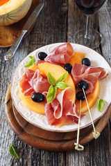 Parma ham with melon and wineglass