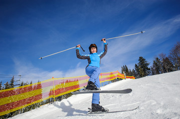 Happy active female skier on a sunny day at ski resort against ski lift and mountains background on a sunny day. Girl raised her arms as sign of success. Winter sports concept.