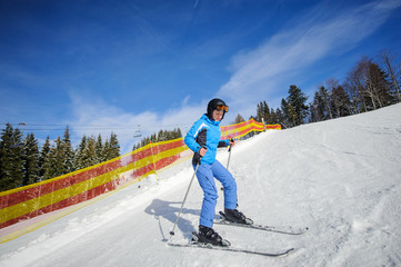 Athlete female skier learning to ski on a sunny day at ski resort with ski lift and mountains on the background. Winter sports concept. Carpathian Mountains, Bukovel