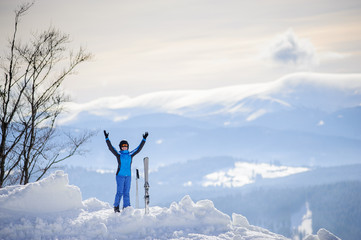 Happy skier standing on the top of the mountain with her arms lifted up against the background of beautiful winter mountains. Carpathian Mountains, Bukovel, Ukraine