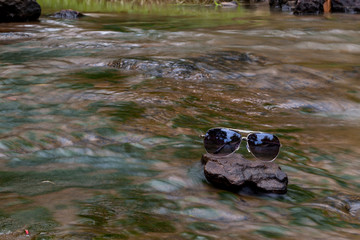 Black glasses lay on a stone waterfall.