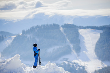 Rear view of skier standing on top of the mountain and enjoying the view on beautiful winter mountains on a sunny day. Winter sports concept. Ski resort