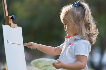 маленькая девочка рисует красками