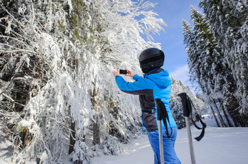 Rear view of woman taking picture with her cell phone in the winter forest with beautiful trees on ski slope. Winter sports concept. Carpathian Mountains, Bukovel, Ukraine