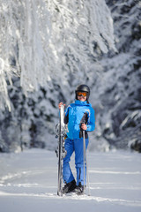 Full length portrait of young happy female skier standing enjoying sunny day against beautiful snow covered trees on the background. Woman is holding her skis in one hand and ski poles in another.