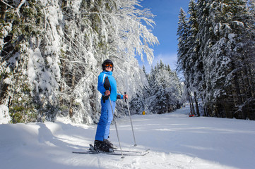 Young female skier on a ski slope in the forest with big beautiful trees covered in snow. Winter sports concept. Wide angle. Carpathian Mountains, Bukovel, Ukraine