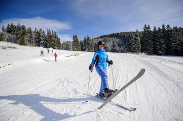 Wide shot of woman skier on a ski slope at ski resort on a sunny day. Winter sports concept.