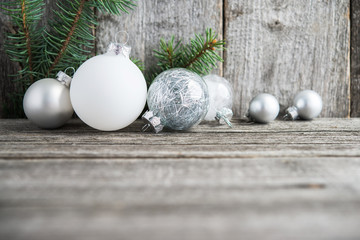 Silver and white christmas ornaments, xmas tree on rustic wood background. Merry christmas card. Winter holiday theme. Happy New Year.