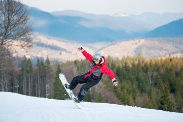 Man snowboarder in the moment of falling at the ski slope. High mountains, forest and hills on background. Extreme freeride
