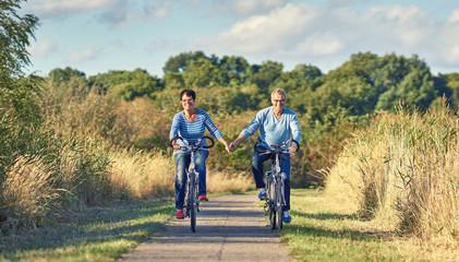 Senioren fassen sich bei der Hand beim Radfahren