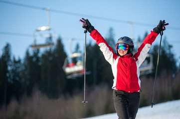 Smiling female skier wearing helmet, red jacket and ski goggles standing on snowy slope with hands raised up in sunny day with forest and blue sky in background. Close-up
