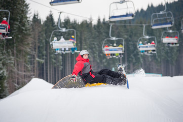 Snowboarder falls on the slopes during the jumping with ski lifts in background, extreme sport, Bukovel, Ukraine